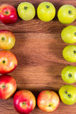 Ripe apples on a path lined with frame on the wooden background. Royalty Free Stock Photo