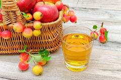 Ripe apples in a wicker basket and a glass of apple juice on a w Stock Photography
