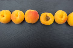 Ripe apricot on black background of slate or stone Royalty Free Stock Photography