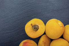 Ripe apricot on black background of slate or stone Stock Images