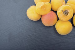 Ripe apricot on black background of slate or stone Royalty Free Stock Image