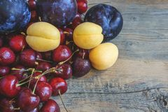 Ripe apricot cherry fruit and plum on a beautiful wooden background. Copy space. The concept of healthy eating Royalty Free Stock Photography