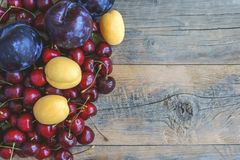 Ripe apricot cherry fruit and plum on a beautiful wooden background. Copy space. The concept of healthy eating Stock Photos