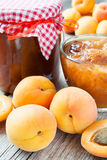 Ripe apricot fruits and jar of jam on table Stock Images