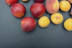 Ripe apricot and nectarine on black background of slate or stone Stock Photo