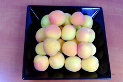 Ripe apricots on a black plate Royalty Free Stock Photos