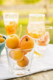 Ripe apricots in glass against  background of drinks Stock Photos