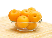 Ripe apricots in a glass bowl. On a white background Royalty Free Stock Image