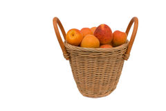 Ripe apricots isolated on a white. Ripe apricots in a wattled basket isolated on a white background Royalty Free Stock Photos