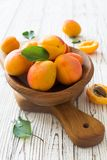 Ripe apricots in wooden bowl. On white wood background close up Royalty Free Stock Photos