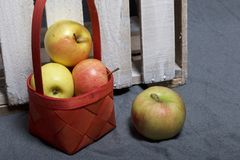 Ripe aromatic apples on a gray cloth. Nearby is a wooden box, knocked out of the boards. Ripe aromatic apples on a gray cloth. Nearby is a wooden box, knocked stock photo