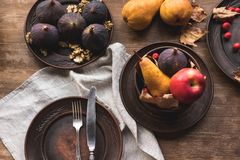 Ripe autumn fruits on table. Top view of ripe seasonal fruits on plates on wooden table Stock Photos