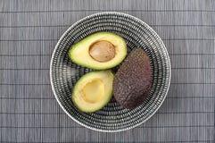 Ripe avocado on ceramic plate. Closeup. Halves of ripe avocado on porcelain plate. Closeup Royalty Free Stock Image