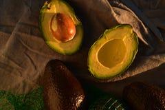 Ripe avocado cut into halves. Still life with whole avocados and one avocado cut into halves Royalty Free Stock Photography