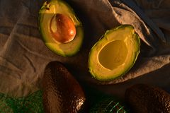 Ripe avocado cut into halves. Still life with whole avocados and one avocado cut into halves Stock Image