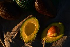 Ripe avocado cut into halves. Still life with whole avocados and one avocado cut into halves Stock Photo