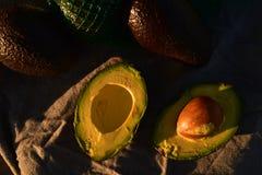 Ripe avocado cut into halves. Still life with whole avocados and one avocado cut into halves Royalty Free Stock Photo