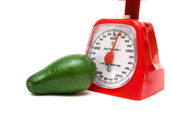 Ripe avocado and kitchen scales on a white background Royalty Free Stock Photo