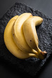 Ripe Bananas on a Black Stone Plate Royalty Free Stock Images