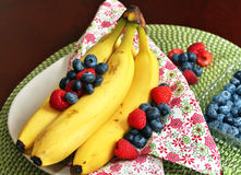 Ripe Bananas with blueberries and raspberries Royalty Free Stock Photography