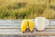Ripe bananas and coffee cup on the wooden table outdoors Royalty Free Stock Images