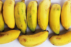 Ripe bananas are cut together in a yellow background.  Stock Photos