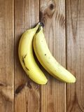 Ripe bananas on a wooden background. Two bananas lie on a wooden tablen Royalty Free Stock Photos