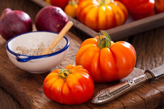 Ripe beef tomatoes with a knife, onions and salt Royalty Free Stock Photo
