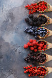 Ripe berries blueberries, raspberries, currants, blackberries. And strawberries in waffle cones with space for text, top view Stock Images