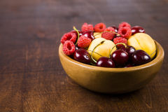 Ripe berries in a plate on a wooden table. Stock Photo