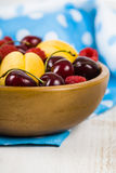 Ripe berries in a plate on a wooden table. Royalty Free Stock Photography