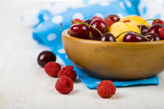 Ripe berries in a plate on a wooden table. Stock Photography