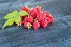 Ripe berries of raspberry garden. Rustic background. Red fresh raspberries on rustic wood background. natural ripe organic berries with green leaves Royalty Free Stock Photo