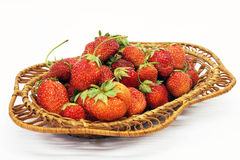 Ripe berries of the strawberries on white background. Mature berries of the strawberry in braided plate are insulated on white background Royalty Free Stock Photo