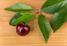 Ripe berries of sweet cherry with leafs on board Stock Images