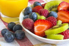 Ripe berry and kiwi with orange juice Stock Photography