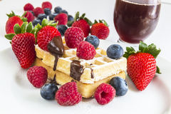 Ripe berry, some of on a waffle and behind white plate red fruit. Ripe berry of raspberries, strawberries and blueberries, some of on a waffle and behind white Royalty Free Stock Photo