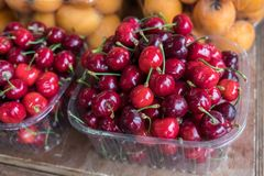 Ripe black cherries in plastic boxes sold at local market. Ripe black cherries in plastic boxes sold at local city market royalty free stock images