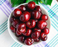 Ripe black cherries in a white bowl on a light background. Stock Photo
