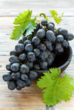 Ripe black grapes in the old bowl. Stock Photography