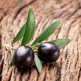 Ripe black olives with leaves. Stock Images