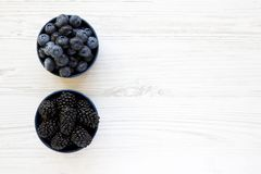 Ripe blackberries and blueberries in blue bowls over white wooden background, top view. Summer berry. From above, flat, overhead. Copy space and text area Stock Image