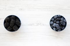 Ripe blackberries and blueberries in blue bowls on white wooden table, top view. Summer berry. From above, flat, overhead. Space for text Royalty Free Stock Image