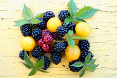 Ripe blackberries and plums. On a wooden stand Stock Images