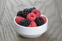 Ripe blackberries and raspberries in white bowl on old oak table. Rustic style Royalty Free Stock Photo