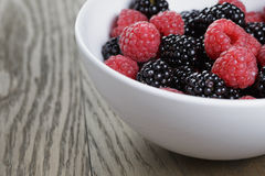 Ripe blackberries and raspberries in white bowl on old oak table Royalty Free Stock Photo
