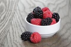 Ripe blackberries and raspberries in white bowl on old oak table Stock Images