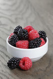 Ripe blackberries and raspberries in white bowl on old oak table Royalty Free Stock Image