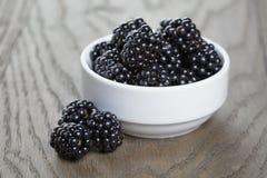 Ripe blackberries in white bowl on old oak table Stock Image