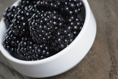 Ripe blackberries in white bowl on old oak table Stock Photo